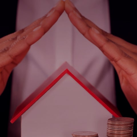 Hands covering a house and money